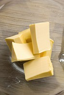 Blocks of butter sit in a glass mixing bowl.