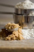 Brown sugar spills out of a measuring spoon with stacked measuring cups of flour in the background.