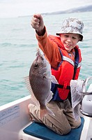 A young boy who has just caught a fish.