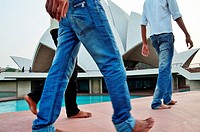 Indian visitors walking barefoot in front of Lotus Temple, India.
