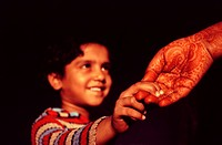 Daughter holding the hand of her mother. Rajasthan, India. The mother has a henna design on her hand.