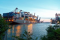 Ships moored at the Eurogate and Burchardkai container terminals in the port of Hamburg, Germany, at sunset in summer