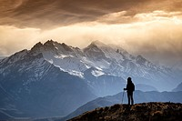 Silhouette of a trekker watching the mountains in the evening sun light. Nepal, Gandaki, Upper Mustang (near the border with Tibet). Model Released.