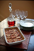 eggplant parmesan in a casserole dish with wine and serving plates.