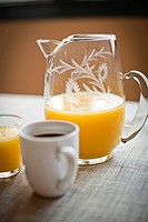 freshly squeezed orange juice in glass pitcher with coffee in mug.