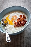 bowl of grits with bacon and egg on top.