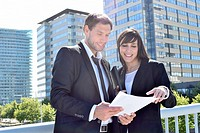 Businessman and businesswoman look over paperwork while standing outside.