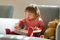 18 months old baby girl looking and pointing at inside a book.