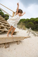 Almost 3 years old little girl jumping from a stair on a beach in Menorca, Spain.