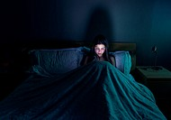 Teenage girl browsing the internet late at night in bed.
