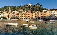 Portofino, Ligurian Coast, Italy, Port, Boats, Colourful homes, Reflections in Sea, Backdrop hillsides with pines and beautiful houses, Horizontal, Bl...