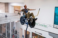 A man rides on a tightrope on sky bike, The Franklin Institute, Philadelphia, Pennsylvania, PA, USA, North America.
