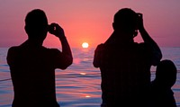 Photographing sunrise. Dolphin watch sunrise tour, Cala Ratjada, Mallorca, Balearic islands, Spain in July.