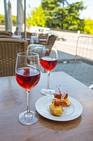 Spanish aperitif: two glasses of rose wine with tapa in a terrace. Madrid, Spain.