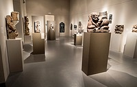 A museum room full of imposing and ancient statues.