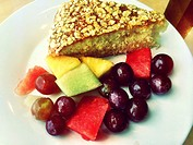 Slice of cake and fresh fruit pieces on plate.