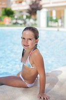 Pretty young girl in swimming pool smiling at camera