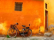Bicycle propped against an orange colored wall in Pistoia, Tuscany.