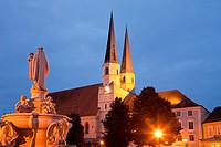 fountain of mary and Collegiate church St. Philipp and Jacob on Kapellplatz square in Altoetting at night, Upper-Bavaria, Bavaria, Germany, Europe.