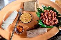 Traditional Ethiopian meal of ´Kitfo´ served with cottage cheese, banana bread, chilli powder and injera.