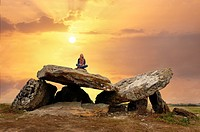 young girl sitting on a Megalithic Dolmen at sunrise, locality Le Carroir Bon Air, commune of Ligre, near Chinon and Richelieu, Indre-et-Loire departm...