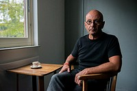 Tilburg, Netherlands. Portrait of a bald man wearing glasses, drinking a cup of coffee while sitting at a small table near the window.