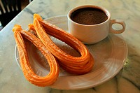 Some churros sprinkled with sugar and served with thick hot chocolate, a typical fried-dough pastry breakfast or snack in Madrid and many other Spanis...