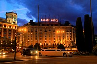 A limousine crosses the Plaza Cánovas del Castillo in Madrid, next to the fountain of Neptune (1786) and the five-star hotel Westin Palace Madrid, bui...
