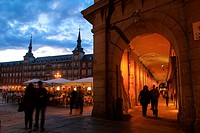 Cloudy twilight on the Plaza Mayor of Madrid seen from Gerona street next to some of many restaurants placed under the porticoes facing the square.