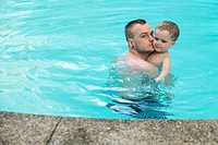 Father with his toddler boy in the swimming pool.