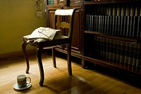 Reading room with chair, ancient open book with glasses and a cup, Madrid, Spain