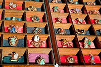 Colorful assortment of jewelry on wooden display full of rings.
