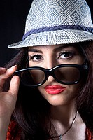 Woman wearing trendy small hat and sunglasses.