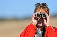 Woman vieing through binoculars, Hwange, Zimbabwe, Africa
