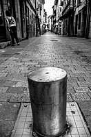 B/W image of Mayor Street of Llanes, a pile to prevent the passage of cars. Llanes, Asturias, Spain.