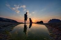 A man and his best friend enjoy the midnight sun on Uttakleiv Beach in the Lofoten Islands, Norway.