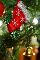 A small decorated Christmas stocking is hanging on the Christmas tree.