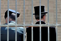 A guardia civil (policeman) and a man with top-hat behind bars in San Lorenzo de El Escorial (Madrid), Spain.