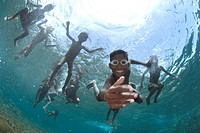 Boy with goggles wanting to shake hands and children swimming and playing in sea with sun in background, Boardroom dive site, Pura Island, near Alor I...