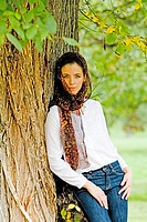 Young woman standing under tree. Woman in a dark scarf with white blousee and blue jeans stands under a large old tree.