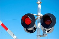 Flashing warning lights at a railroad crossing while the gate is being lowered.