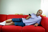 A senior citizen relaxing on a couch with a remote control in hand and potatoes on the couch.