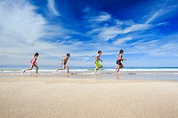 children running along sandy beach, Scotland.
