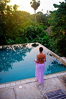 Young attractive woman enters an infinity edge swimming pool at The Dutch House, Galle, Sri Lanka.