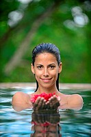 Young attractive woman holding red flowers in an infinity edge swimming pool. The Dutch House, Galle, Sri Lanka.