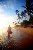 Young woman walking on Hikkaduwa beach at sunset, Sri Lanka.
