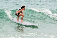 A six year old girl surfing.