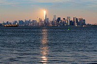 Lower Manhattan skyline at sunset from Staten Island ferry, New York City, USA.