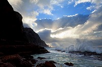Landscape photo of a wave crashing against the rocks under a dramatic sunrise sky. Cape Point National Park, Cape Town, South Africa.