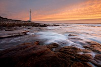 Wide angle landscape photo of a lighthouse below a sunset sky. Kommetjie, Cape Town, South Africa.